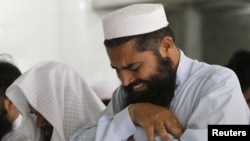 A man cries as he offers funeral prayers with others for the dead Taliban supreme leader Mullah Mohammad in Pakistan on July 31.