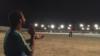 Afghanistan -- Players and spectators enjoy a nighttime cricket match in Lashkar Gah's Wazir Akbar Khan stadium.