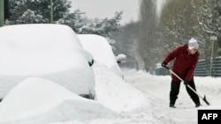 Женщина расчищает снег у своего дома. Иллюстративное фото.