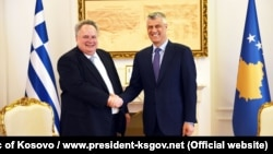 Greek Foreign Minister Nikos Kotzias (left) shakes hands with Kosovar President Hashim Thaci in Pristina on April 12.
