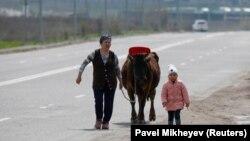 Коронавирус карантині кезінде Алматының шетінде сиыр жетектеп келе жатқан әйел мен бала. 2020 жылдың сәуірі. Көрнекі сурет.