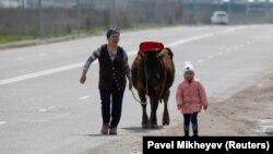 Коронавирус карантині кезінде Алматының шетінде сиыр жетектеп, бала ертіп келе жатқан әйел. 14 сәуір 2020 жыл. Көрнекі сурет.