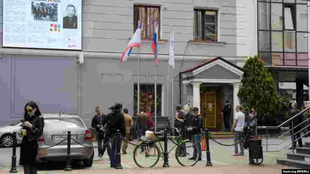 Очередь перед отделением банка «Россия» на проспекте Кирова. Чтобы люди не скучали, им транслируют на большой экране, установленном на фасаде здания, документальный «Бессмертный полк»