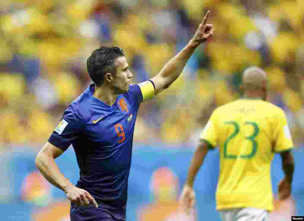 Robin van Persie of the Netherlands celebrates after scoring a goal from a penalty kick during their 2014 World Cup third-place playoff against Brazil at the Brasilia national stadium in Brasilia