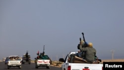 Rebels travel in a convoy on their way to Sirte.