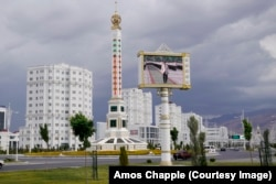 A giant thermometer on a roundabout in Ashgabat. The screen in the foreground played a loop of autocratic leader Gurbanguly Berdymukhammedov attending official ceremonies.