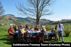 Туристи за столом із місцевими мешканцями в селі у Карпатах