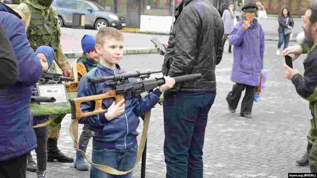 Севастопольский мальчик позирует со снайперской винтовкой