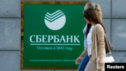 Women walk past a Sberbank office in Moscow on September 12.