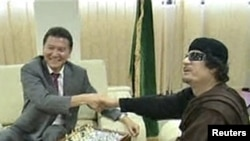 A screen grab showing Libyan leader Muammar Qaddafi shaking hands with Kirsan Ilyumzhinov, the president of the international chess federation, in Tripoli