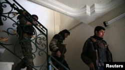 Rebel fighters carry their weapons down a staircase on January 2 in the eastern Damascus suburb of Ghouta.