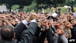 Tunisia -- Demonstrators hold up their hands as if they are handcuffed and shout slogans in front the Interior ministry in Tunis, 14Jan2010