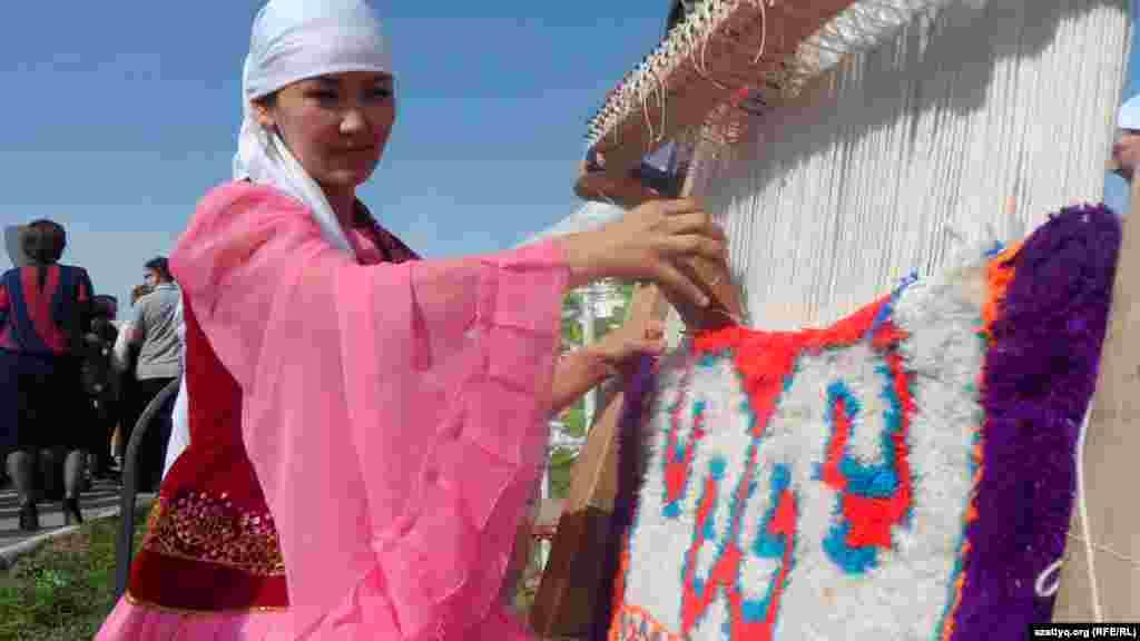 Женщина ткёт традиционный войлочный ковер.