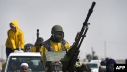 Rebel fighters leave the town of Ajdabiya on April 6.
