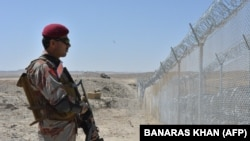 A Pakistani Army soldier stands guard along a border fence at the Afghan border near the Punjpai area of Quetta in Balochistan Province.