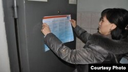 A social worker with the NGO Sana Sezim hangs up a flyer on how to avoid becoming a victim of human trafficking and labor exploitation at a police station in Shymkent, Kazakhstan.
