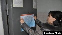 """Сотрудник НПО """"Сана Сезим"""" вывешивает в отделении полиции в Шымкенте информационный баннер о том, как не стать жертвой торговли людьми."""