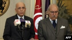 Tunisian Prime Minister Mohammed Ghannouchi (left) addresses the nation on state television, flanked by the interim president, Fouad Mebazza