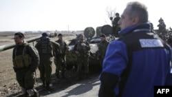 Представитель Специальной мониторинговой миссии ОБСЕ наблюдает за украинскими военными. Донецкая область, Украина, 27 февраля 2015 года.