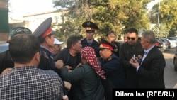 Полиция қызметкерлерінің белсенді Нұржан Мұхамедовті сот залына күштеп апаруға тырысып жатқан сәті. Шымкент, 25 қазан 2019 жыл