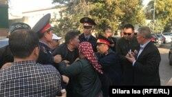 Нуржан Мухамедов (в центре) в момент захвата сотрудниками полиции, которые затем заведут его в зал суда. Шымкент, 25 октября 2019 года.