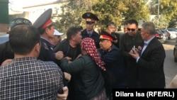 Полиция пытается доставить активиста в зал суда. Шымкент, 25 октября 2019 года.
