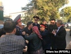 Полиция қызметкерлерінің Нұржан Мұхамедовті сот залына күштеп апаруға тырысып жатқан сәті. Шымкент, 25 қазан 2019 жыл.