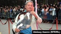 Булат Нусумбек, режиссер документального фильма о Шакене Айманове, идет по красной дорожке с плакатом своего фильма. Алматы, 15 сентября 2014 года.