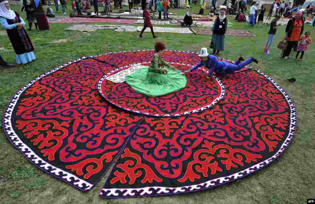 A woman wearing a traditional Kyrgyz dress sits on felt carpets at the seventh International Festival of Kyrgyz National Applied Arts in the village of At-Bashi, 400 kilometers from Bishkek, on June 28. (AFP/Vyacheslav Oseledko)