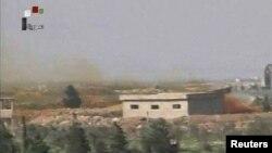 Кадр із відео сирійського державного телебачення, на якому видно дим, що йде від авіабази сирійських військ поблизу Хомса після авіаудару сил США, 7 квітня 2017 року
