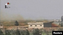 Кадр из видео сирийского государственного телевидения, на котором виден дым, идущий от авиабазы сирийских войск вблизи Хомса после авиаудара сил США, 7 апреля 2017