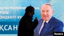 Человек у баннера с портретом президента Казахстана Нурсултана Назарбаева. Иллюстративное фото.