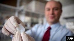 Larry Bonassar, profesor, drži u ruci uho napravljeno 3D tehnikom