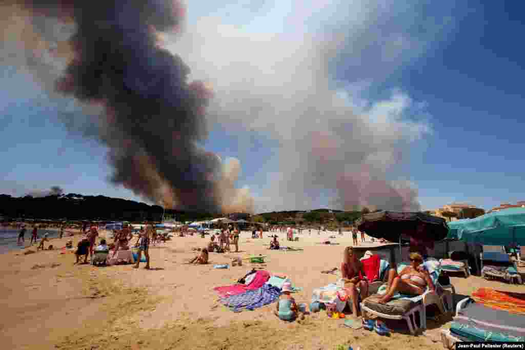 Smoke fills the sky above a burning hillside as tourists relax on the beach in Bormes-les-Mimosas, France, on July 26. (Reuters/Jean-Paul Pelissier)