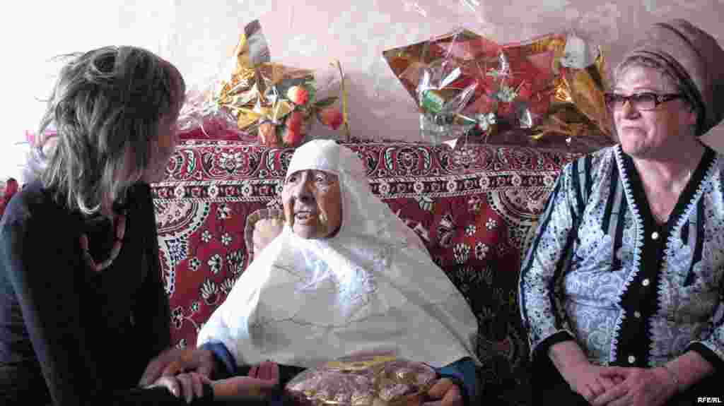 Чиновники городского собеса беседуют с Сахан Досовой в тесной квартире, где живут 11 человек.