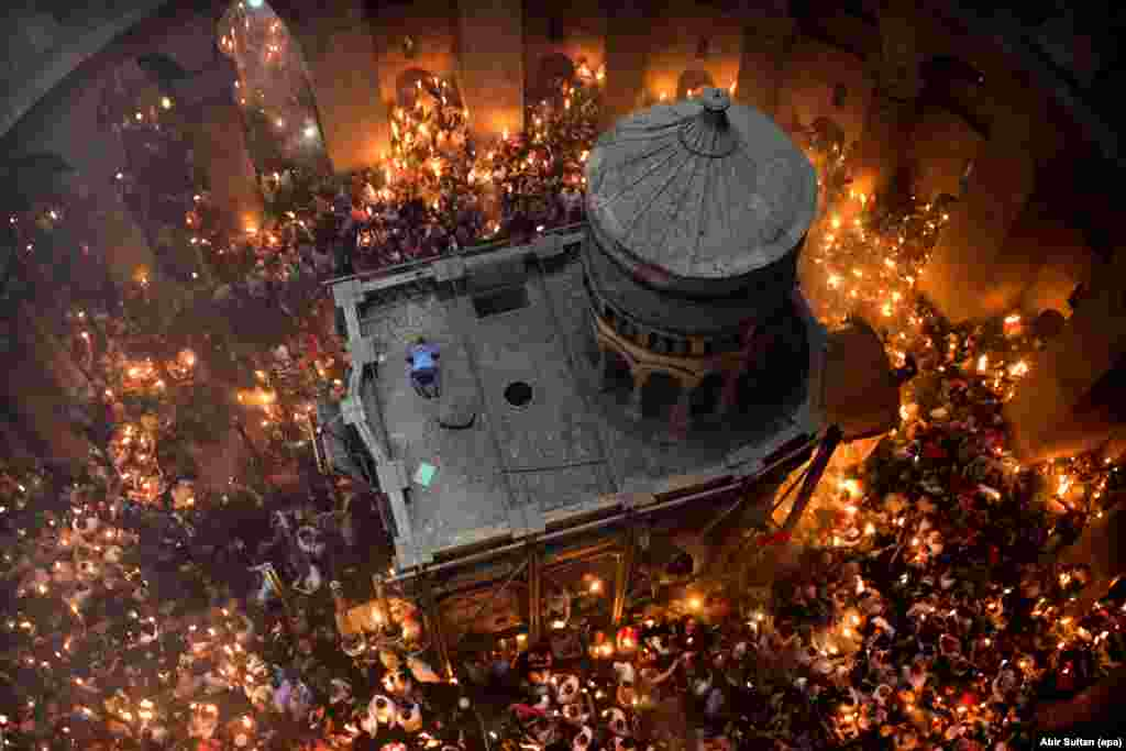 "For Abir Sultan, local contacts were key to this image of Jerusalem's annual Miracle of the Holy Fire. ""I know the deputy patriarch very well so I asked him if I could go up the top, looking down at the ceremony,"" the epa photographer says. When a man climbed onto the roof of Jesus's tomb during the Orthodox Christian ritual, Sultan knew he had that ""little something different.""   ""He dropped onto the ground almost like a Muslim praying,"" he recalls. ""It was just for a second."" As Sultan worked, some nuns stood next to him holding unlit candles. ""In the ceremony the people are hoping for God's light to reach them -- when your candle catches fire it's like a blessing. These nuns were standing up there with me, 30 meters above the flames. There is really no chance their candles will light, but every time I shoot this ceremony they're there, waiting for God's blessing."""