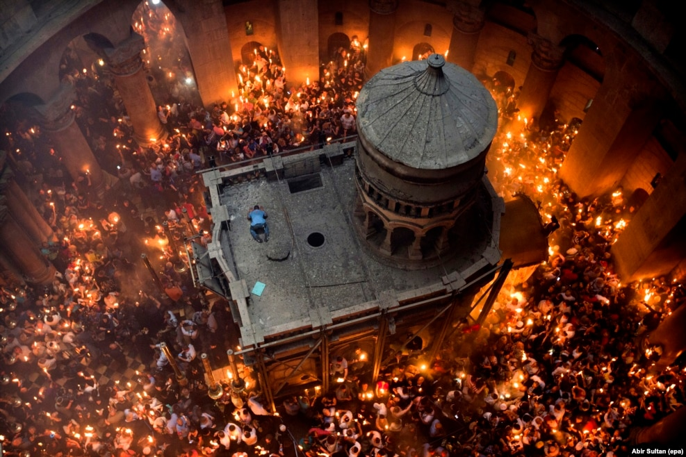 """For Abir Sultan, local contacts were key to this image of Jerusalem's annual Miracle of the Holy Fire. """"I know the deputy patriarch very well so I asked him if I could go up the top, looking down at the ceremony,"""" the epa photographer says. When a man climbed onto the roof of Jesus's tomb during the Orthodox Christian ritual, Sultan knew he had that """"little something different.""""  """"He dropped onto the ground almost like a Muslim praying,"""" he recalls. """"It was just for a second."""" As Sultan worked, some nuns stood next to him holding unlit candles. """"In the ceremony the people are hoping for God's light to reach them -- when your candle catches fire it's like a blessing. These nuns were standing up there with me, 30 meters above the flames. There is really no chance their candles will light, but every time I shoot this ceremony they're there, waiting for God's blessing."""""""