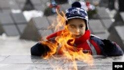 Румынский мальчик, родственник жертвы восстания 1989 года, стоит у Вечного огня, зажженного на Кладбище Революции в городе Тимишоара. 17 декабря 2009 года.