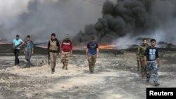 ИМ тобунан бошотулгани жерде мунай куурлары өрттөнүүдө. Сүрөттө Ирак аскерлери. 1-ноябрь, 2016-жыл