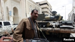 A rebel fighter walks beside a captured pro-government forces tank in Misurata
