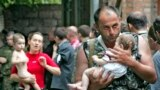 A soldier carries a baby after the hostage-takers released 26 women with their children from the Beslan siege on September 2, 2004.