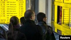 Люди стоят в очереди у обменного пункта в Киеве.