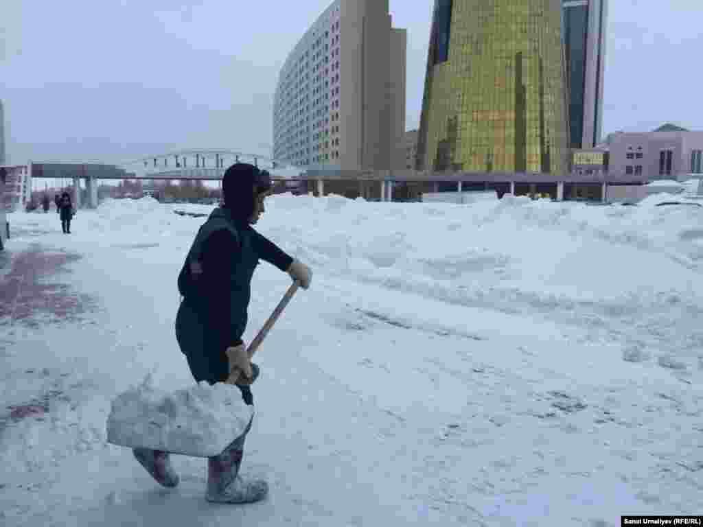 Кайрат Курмангалиев, 50-летний работник «Астана Зеленстрой», расчищает снег на тротуаре напротив Дома министерств. По его словам, он чистит там, «куда начальство направит». Зарплата работника составляет около 80-90 тысяч тенге. Нур-Султан, 28 января 2020 года.