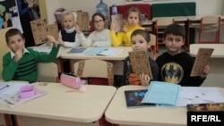 Школярі зі щоденниками, зробленими з переробленої тари