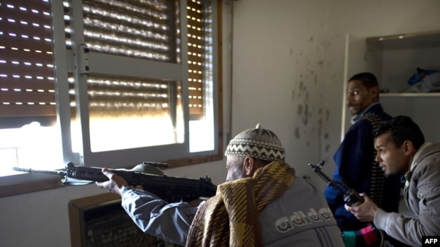 Libyan rebel fighters fire on loyalist snipers from a window in a trashed house on Tripoli Street in Misurata on April 20.