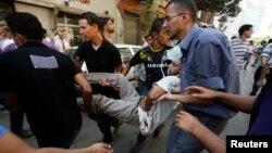Мұхаммед Мурсидің жақтастары жараланған шерушіні әкетіп барады. Каир, 16 тамыз 2013 жыл