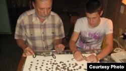 Сергій Санжаров з учнем вивчають знахідки