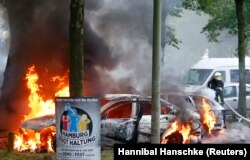 Firefighters work to extinguish burning cars set alight during protests outside the G20 summit in Hamburg on July 7.
