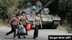 Refugiați georgieni trec prin fața unui tanc rusesc în satul Igoeti, la 50 km de Tbilisi, august 2008