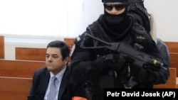Marian Kocner sits surrounded by armed police officers in a courtroom in Pezinok on December 19.